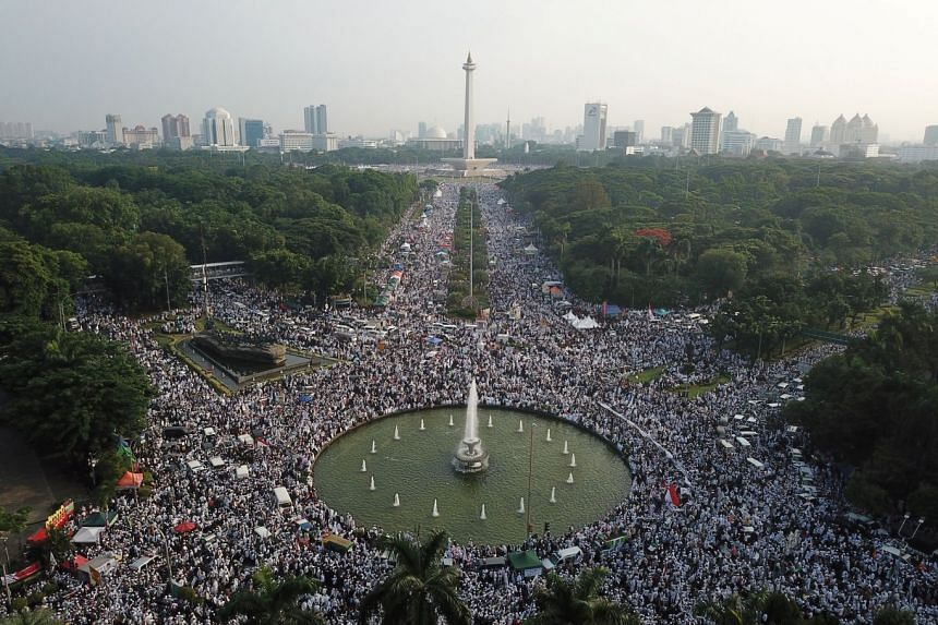 The crowd, many of whom were dressed in white and carrying Islamic flags, started gathering at Jakarta's National Monument from around 3am to hold prayers.