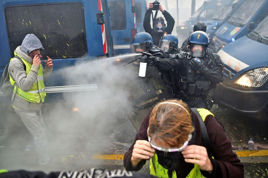 Protesters being sprayed with tear gas by the police on the Champs-Elysees. The avenue was on lockdown, with riot police manning barricades and water cannons. Demonstrators in yellow vests, which have become a symbol of the protest against President