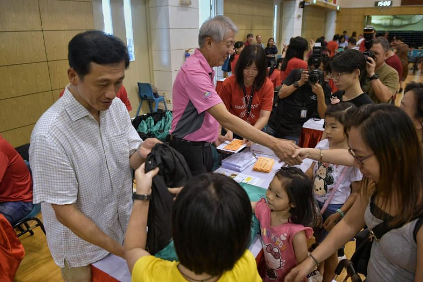 Minister for Education Ong Ye Kung and DPM Teo Chee Hean helping to distribute packs to beneficiaries on Dec 2, 2018.
