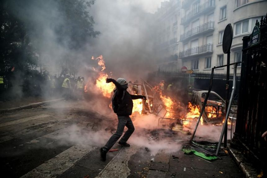 A protester throwing a projectile at riot police during a clash in Paris on Dec 1, 2018.