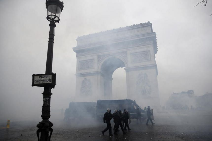 "French riot police passing by the Arc de Triomphe during a clash with ""yellow vest"" protesters in Paris on Dec 1, 2018."