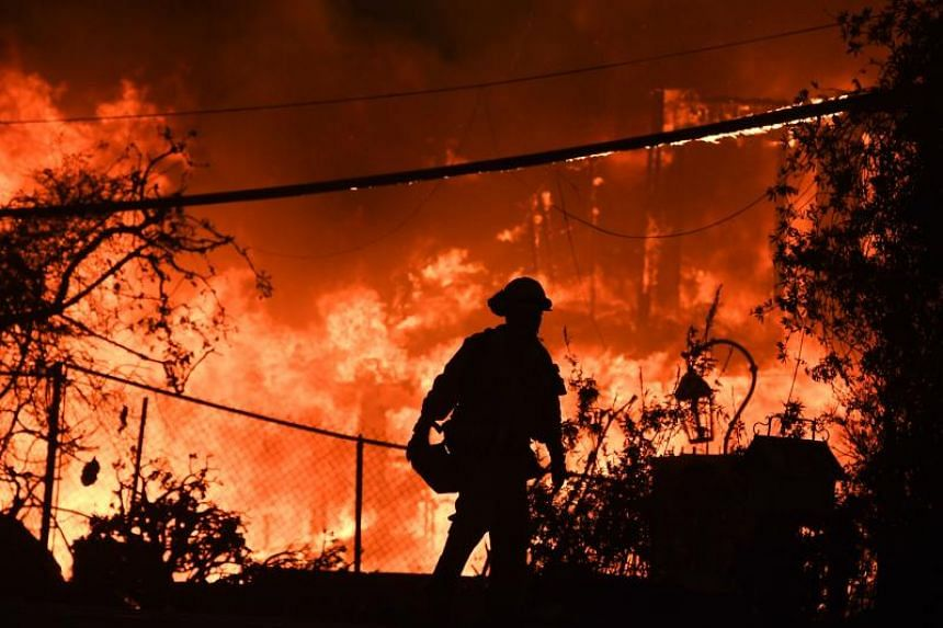 A firefighter is silhouetted by a burning home along the Pacific Coast Highway during the Woolsey Fire in Malibu, California, on Nov 9, 2018.