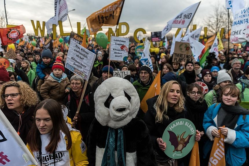 People at a protest in Berlin last Saturday calling for an end to the use of coal power. At the UN climate change summit in Poland, a key issue up for debate is how the fight against climate change is funded, with developed and developing nations sti