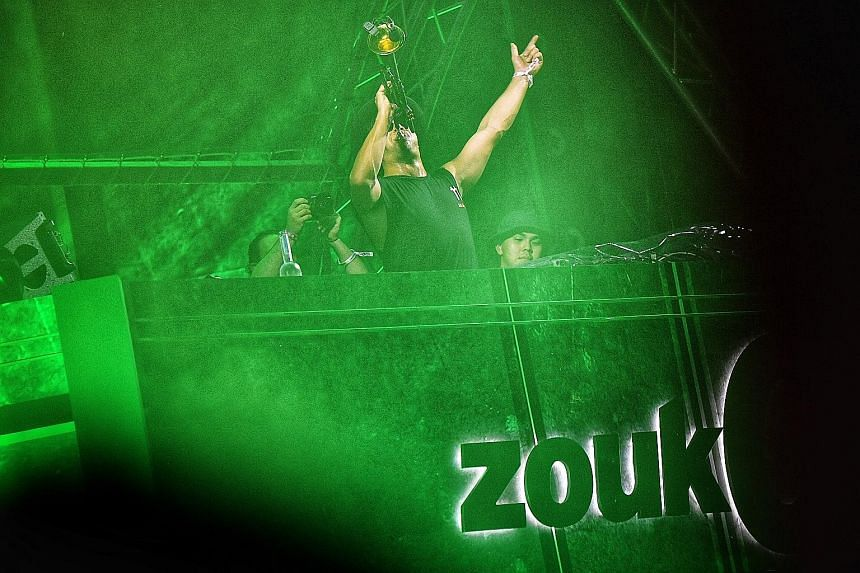 This year's ZoukOut, attended by 20,000 partygoers (above), features one main stage (right) and first-time acts such as Belgian DJ-producer duo DVLM and Swedish duo Galantis. Australian DJ and instrumentalist Timmy Trumpet entertaining concertgoers w