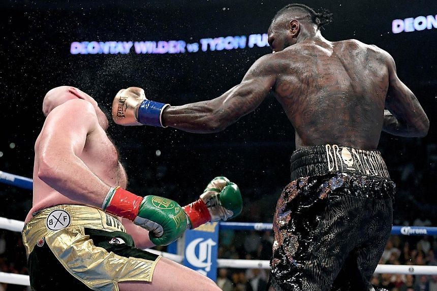 Left: Deontay Wilder knocking Tyson Fury down with a slashing left hook in the 12th round of their WBC heavyweight title fight at Staples Centre in Los Angeles on Saturday. Wilder retained the title after a split draw decision by the judges. Below: A