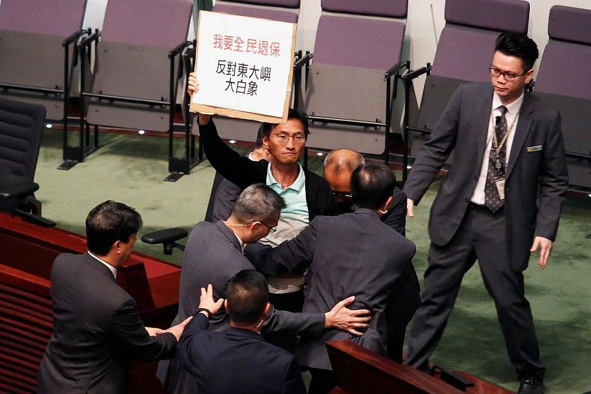 Pro-democracy lawmaker Eddie Chu holding a placard against an East Lantau Metropolis project, while being surrounded by security guards at the Legislative Council in Hong Kong, on Oct 10, 2018.