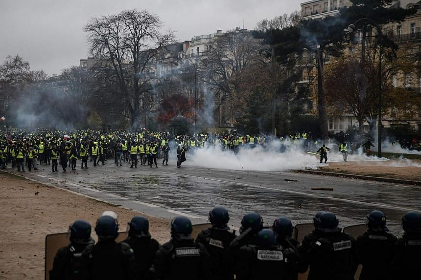Yellow vests protesters face riot police as they demonstrate against rising oil prices and living costs in Paris, France on Dec 1, 2018.