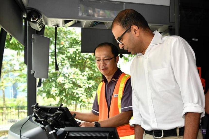 Chief bus captain Chung Sing Loong shows Senior Minister of State for Transport Janil Puthucheary how the mobile application BusNow works on his tablet.