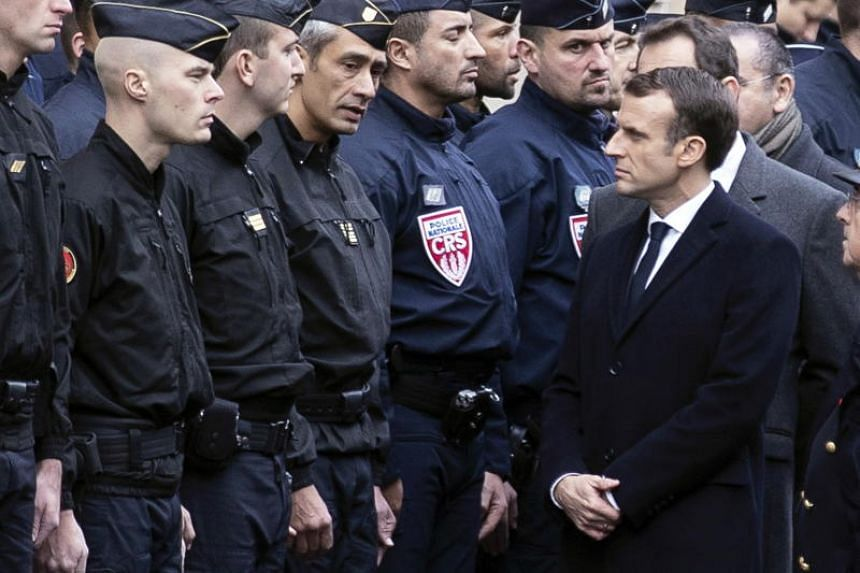 French President Emmanuel Macron (right) talks to riot police officers next to the Champs Elysee in Paris, France, on Dec 2, 2018.
