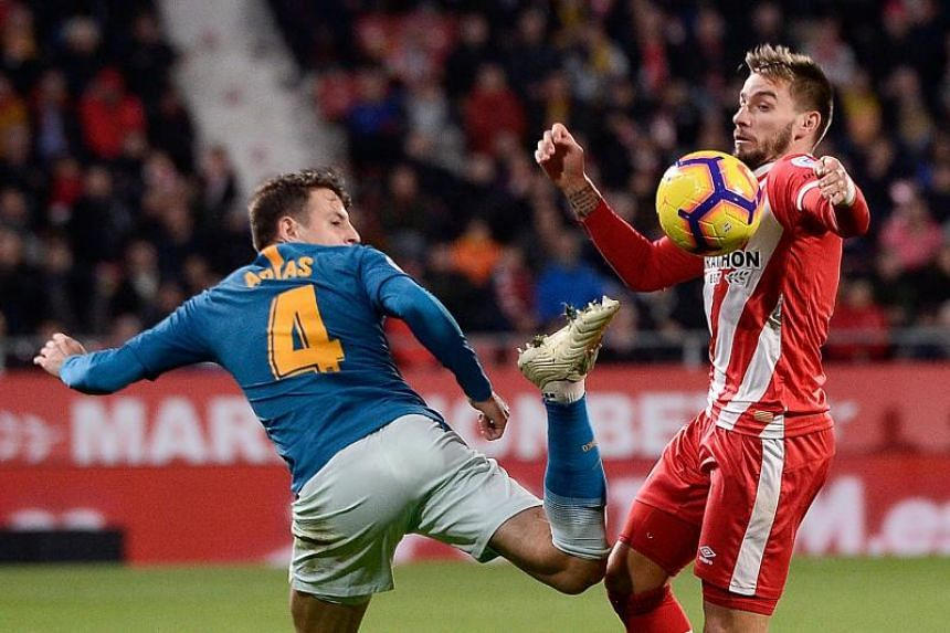 Girona's Spanish midfielder Cristian Portugues (right) challenges Atletico Madrid's Colombian defender Santiago Arias during the match between Girona and Club Atletico de Madrid at the Montilivi stadium in Girona, on Dec 2, 2018.
