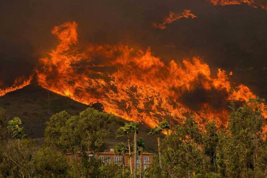 File photo of the Woolsey Fire approaching homes, on Nov 9, 2018, in Malibu, California.