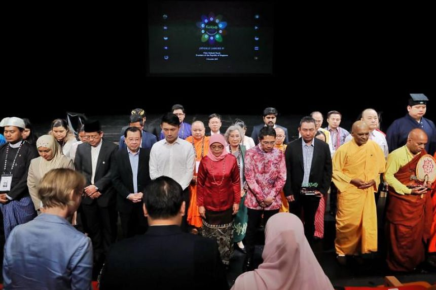 President Halimah Yacob observing a minute of silence with inter-faith practitioners and activists from Asean countries at the launch of the regional inter-faith exchange programme, Faithfully Asean.