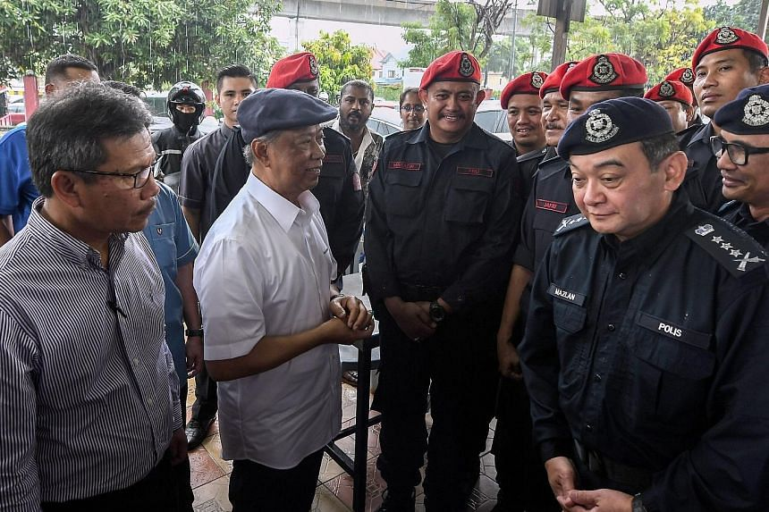 Above: Home Minister Muhyiddin Yassin (in white shirt) speaking with policemen guarding the site of the Sri Maha Mariamman temple yesterday. With him were the Home Ministry's secretary-general Alwi Ibrahim (left) and Selangor police chief Mazlan Mans