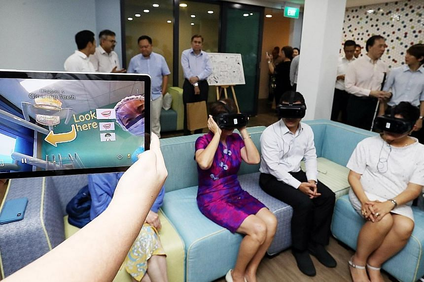 (From far right): National Council of Social Service president Anita Fam, Minister for Social and Family Development Desmond Lee and Ms Denise Phua, Mayor of Central Singapore District, trying out virtual reality goggles used for caregiver training a