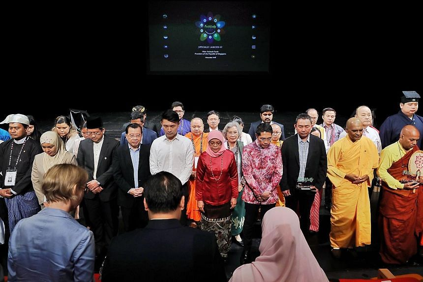 President Halimah Yacob (centre), flanked by Senior Minister of State for Defence and Foreign Affairs Maliki Osman on her left and Senior Parliamentary Secretary for Culture, Community and Youth and Transport Baey Yam Keng to her right, observing one