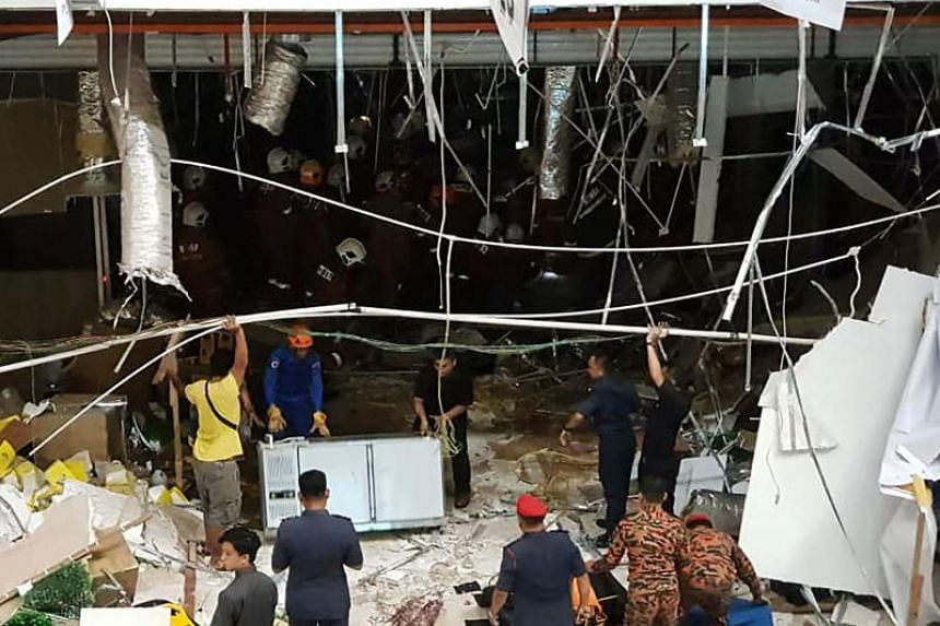 Malaysian security personnel inspect the site after an explosion at the CityOne Megamall in Kuching on Dec 4, 2018.