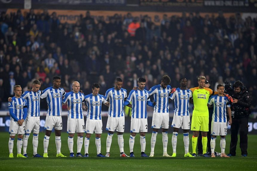 Huddersfield's players observe a minute's silence for to remember the victims of the Leicester City helicopter crash which killed Leicester City Chairman Vichai Srivaddhanaprabha, on Nov 5, 2018.