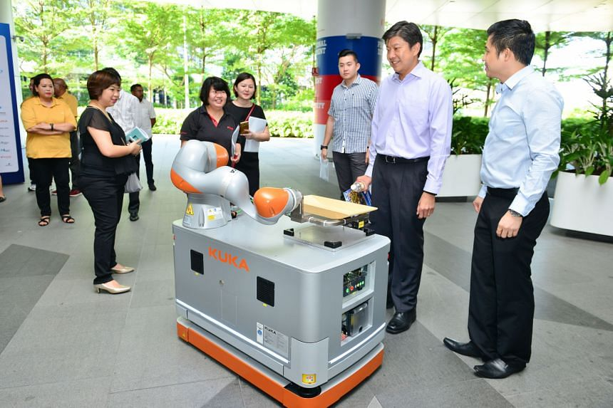 NTUC secretary-general Ng Chee Meng (second from right) touring exhibitor booths on the first day of Marine Week yesterday, at the Devan Nair Institute for Employment and Employability.