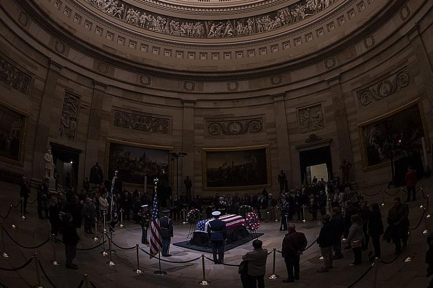 Members of the public paying their respects at the flag-draped casket of former US president George H.W. Bush in the Rotunda of the US Capitol in Washington on Monday.