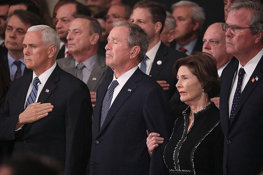 From far left: US Vice-President Mike Pence, former president George W. Bush, former first lady Laura Bush and former Florida governor Jeb Bush watching as the casket of former president George H. W. Bush arrives at the US Capitol Rotunda, where the