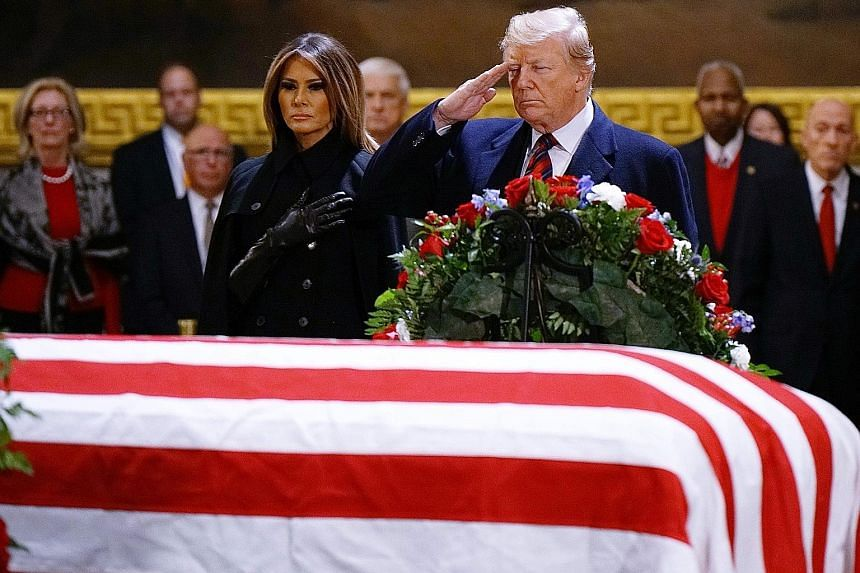 United States President Donald Trump and First Lady Melania Trump paying their respects to former US leader George H. W. Bush. Mr Trump has been effusive in his praise of Mr Bush since his death last Friday.