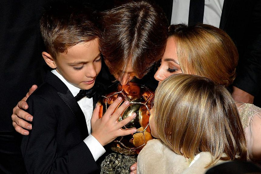Left: Croatian midfielder Luka Modric kissing the Ballon d'Or trophy with his wife Vanja, son Ivano and daughter Ema after Monday's award ceremony in Paris. It was the first time in 10 years that the award did not go to Cristiano Ronaldo or Lionel Me