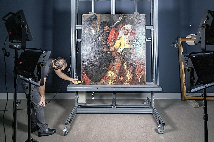 In an undated handout photo provided by Dresden State Art Museums, a photographer takes a high-resolution photo of The Procuress (above), a painting by Vermeer. All authenticated Vermeer paintings, including Girl With A Pearl Earring (far left), can