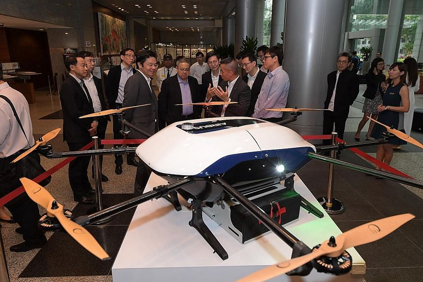A drone exhibit by Airbus at the URA exhibition on innovations in urban logistics yesterday, where Airbus project leader Leo Jeoh gave a presentation to (centre, from left) National Development Minister Lawrence Wong, URA's chairman Peter Ho, chief e