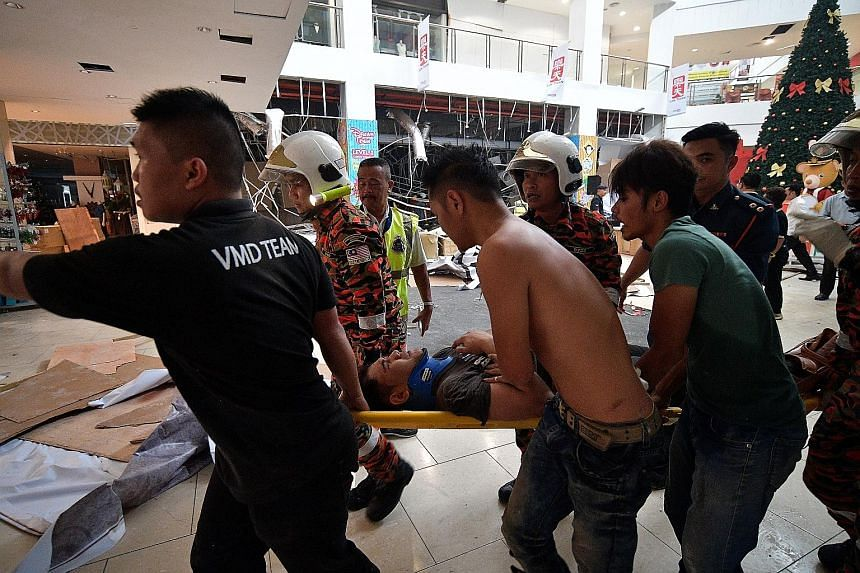 (Above) Investigators and firefighters at the scene after an explosion at the CityOne Megamall in Kuching, Sarawak, yesterday which killed three men. (Below) One of the injured being rushed to hospital. Of the 26 injured, four are in critical conditi