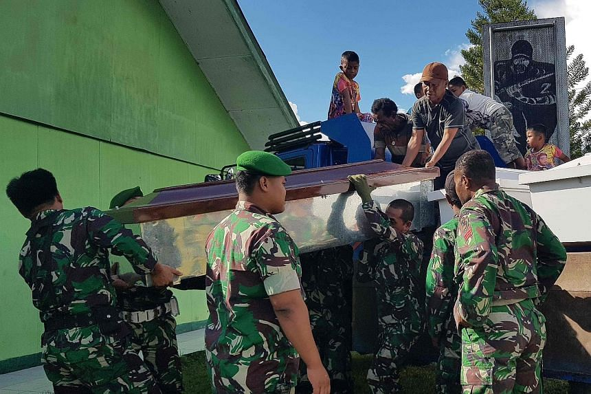 Indonesian soldiers preparing coffins yesterday for at least 24 construction workers, believed to have been killed by separatist rebels in restive Papua province.
