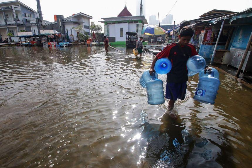 Vendors continuing trading activities despite a tidal flood surrounding Kali Adem port in Muara Angke, North Jakarta.