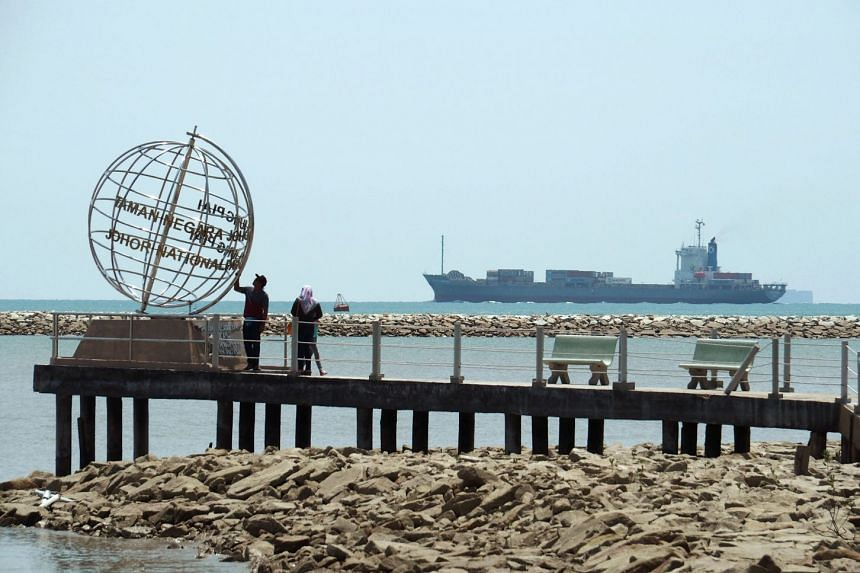 A container ship enters the Singapore Strait, as tourists stand at the southern most point in Johor, on Nov 12, 2016.