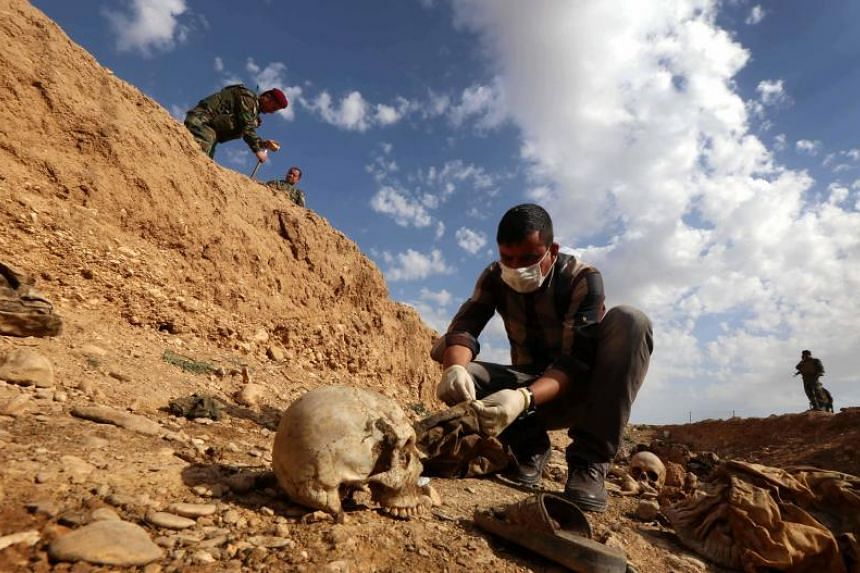 An Iraqi man inspecting the remains of Yazidi who were killed by ISIS, that were discovered in a mass grave, on Feb 3, 2015.