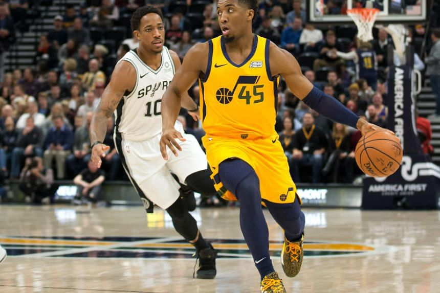 Donovan Mitchell of the Utah Jazz dribbles the ball ahead of San Antonio Spurs guard DeMar DeRozan during the first quarter at the Vivint Smart Home Arena in Salt Lake City, Utah, on Dec 4, 2018.