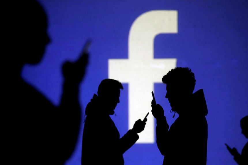 Silhouettes of mobile users are seen next to a screen projection of the Facebook logo.