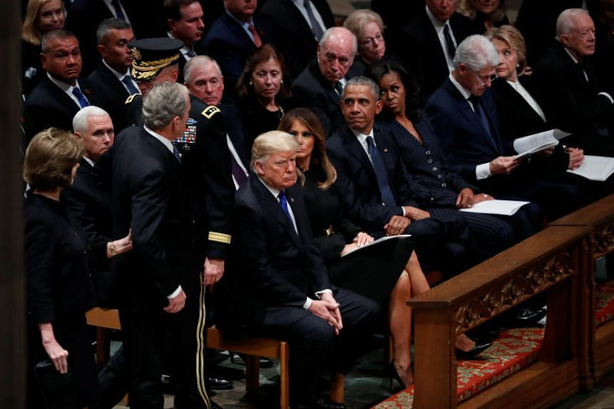 Former president George W. Bush and his wife Laura Bush walk over to greet US President Donald Trump, first lady Melania Trump, and other former presidents and their spouses at the start of the state funeral for his father at the Washington National