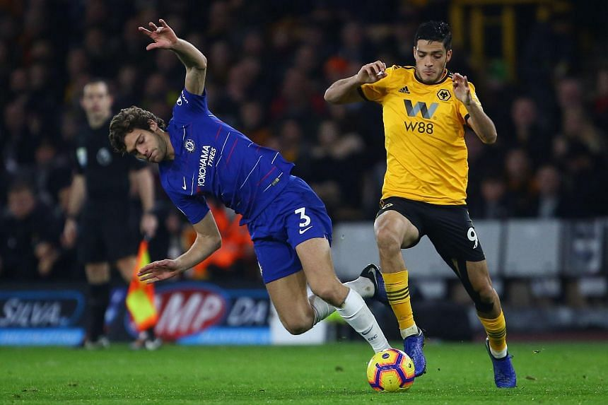 Chelsea's Spanish defender Marcos Alonso (left) challenges Wolverhampton Wanderers' Mexican striker Raul Jimenez during the EPL match between Wolverhampton Wanderers and Chelsea at the Molineux stadium in Wolverhampton, central England on Dec 5, 2018