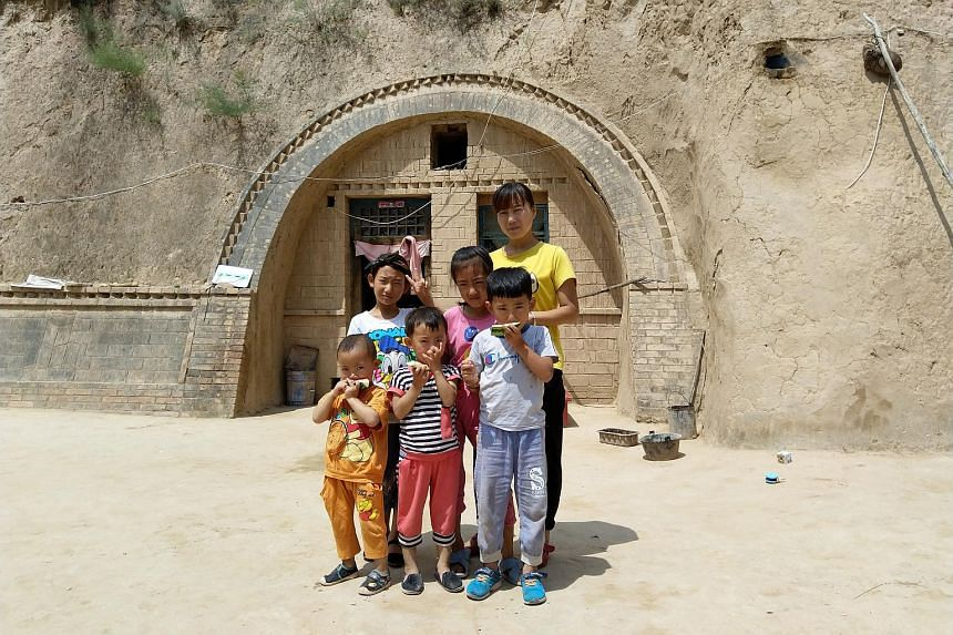 Xu Qirong (in orange), a 34-month-old cousin of Xu Qirui, is also in the early childhood programme. He is pictured here with his family in front of a typical mountain cave home in Qiaochuan township in Gansu's Huachi county.