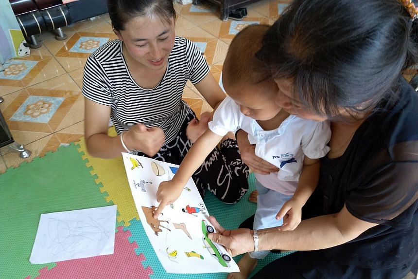 Home educator Zhang Lili, 34, encourages two-year-old toddler Rao Miaoxin during a session with a picture book.