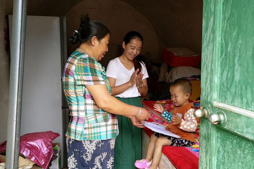 Home educator Fen Na, 32, claps along with two-year-old toddler Liu Zhiyi during a singing session in the girl's home in Chunguan village in Gansu's Huachi county.