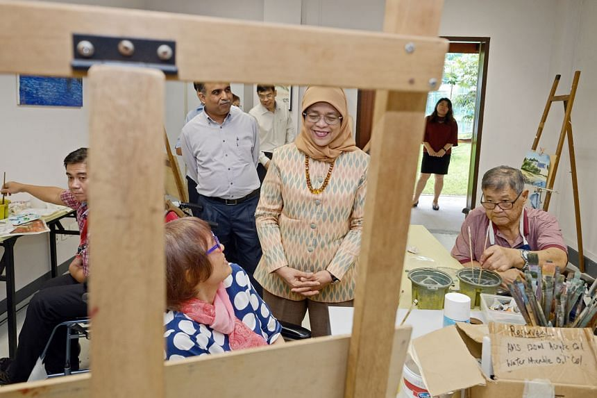 President Halimah Yacob chatting with 78-year-old Daisy Tay Gek Thin during a visit to the Handicaps Welfare Association (HWA) yesterday. The President, accompanied by HWA executive director Subrata Banerjee, was dropping in on an art room where Ms T