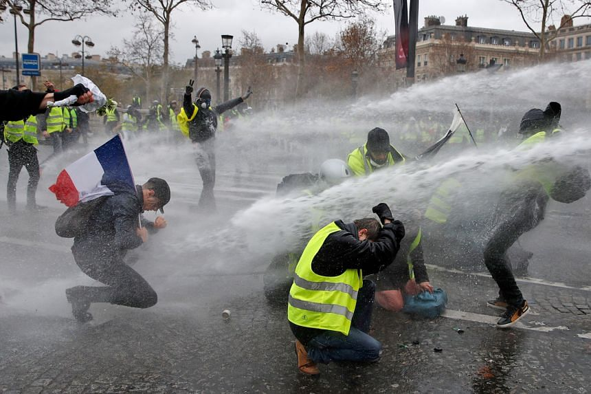 Protesters in yellow vests being hit with water from cannon as they clash with riot police during a demonstration over high fuel prices in Paris last Saturday.