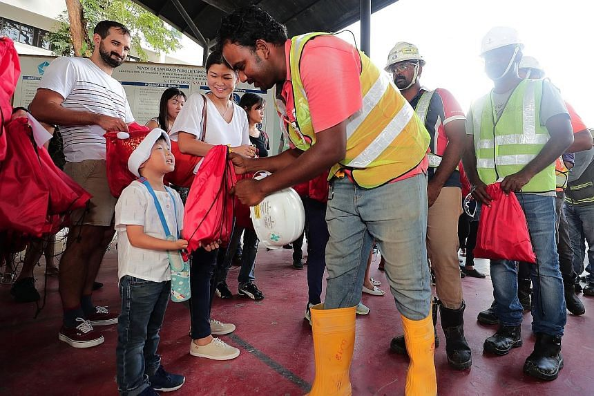 Shen Ruidong, five, and his mother, Madam Khoo Meishan, 35, distributing presents at a Grange Road construction site yesterday. Ms Dipa Swaminathan, ItsRainingRaincoats founder, says she was struck by the care with which the gifts were wrapped.