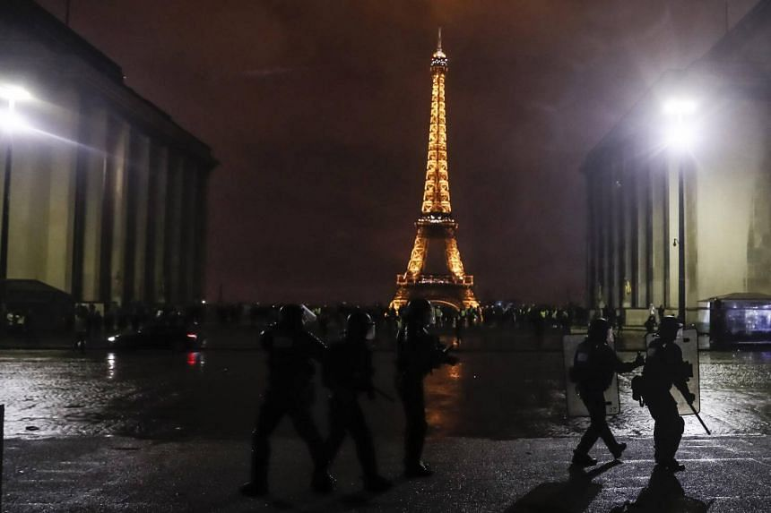 """Riot police take up positions on Place Trocadero near the Eiffel Tower, during clashes with """"yellow vest"""" protesters as well as radical elements from the far left, and far right, and looters, in Paris, France, on Dec 1, 2018."""