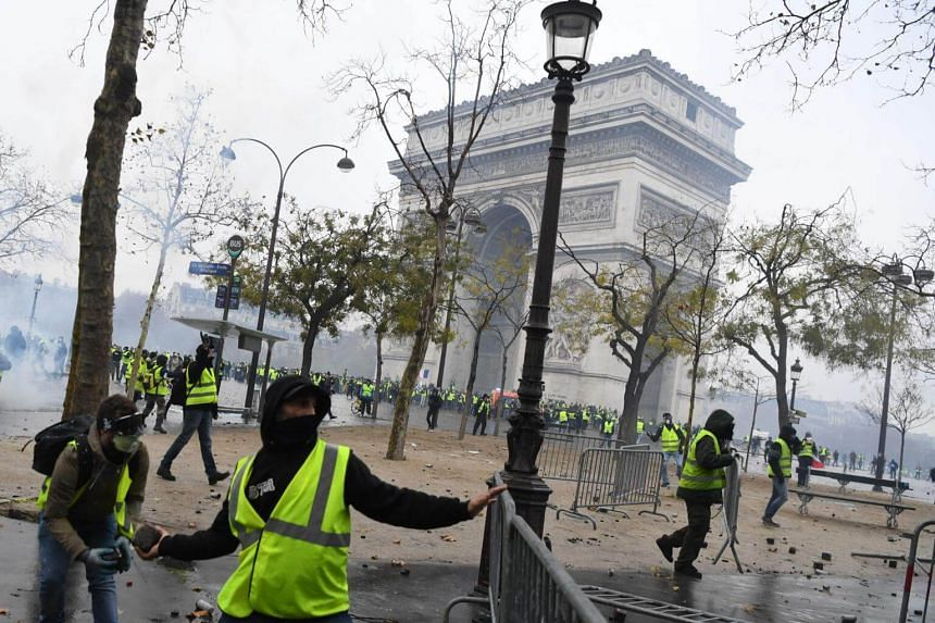 Protesters at the Arc de Triomphe monument in Paris. Images of the rioters throwing cobblestones and fighting police on the Champs-Elysees have shocked viewers across the globe.