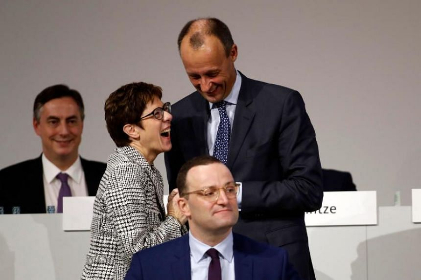 Corporate lawyer and former CDU parliamentary group leader Friedrich Merz (top right), CDU Secretary General Annegret Kramp-Karrenbauer (left) and Health Minister Jens Spahn take part in the CDU congress on Dec 7, 2018 at a fair hall in Hamburg, nort