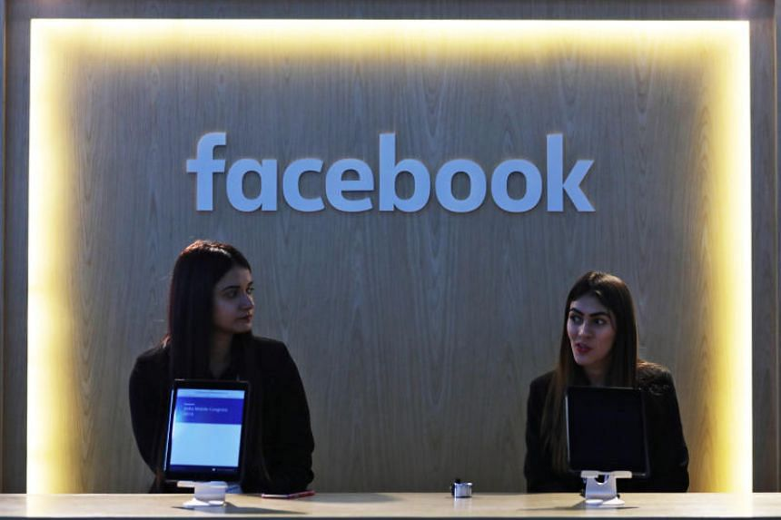 Women wait at Facebook's kiosk at the India Mobile Congress 2018 in New Delhi, India, on Oct 26, 2018.