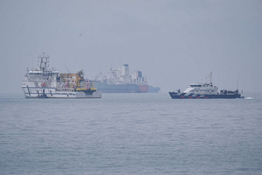 A Malaysian government vessel (left) and a Singapore Police Coast Guard vessel in Singapore territorial waters off Tuas yesterday.