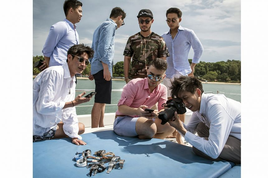 Members of #PatekAcademy, an Instagram affinity group, taking photos of their Patek Philippe watches during a catamaran cruise encircling the nearby islands in the Singapore Strait.