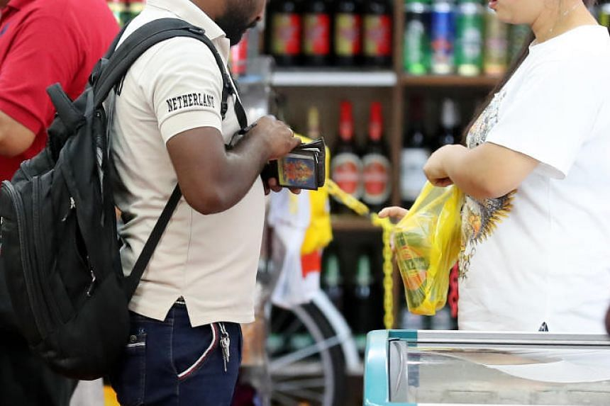A customer buying a can of beer in Little India at about 9pm on Dec 2, 2018. Such transactions are taking place surreptitiously as shops in Little India are barred from selling liquor past 7pm on weekends and from 10.30pm on weekdays.